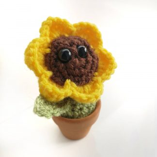 bright yellow crochet flower with expressive black eyes