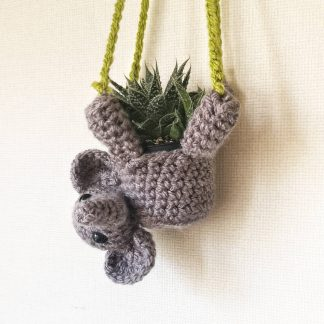 a small grey crochet elephant plant hanger suspended by green crochet strings attached to a wooden hoop for hanging