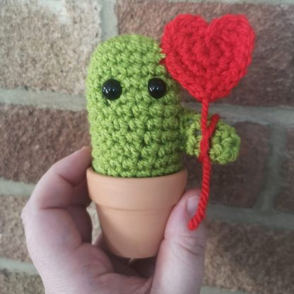 bright green crochet cactus holding a red heart shaped crochet baloon